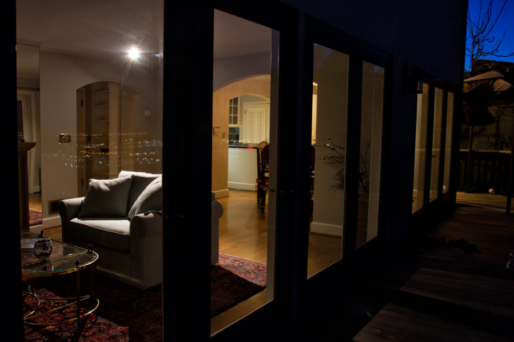 Lit home interior through french doors at night