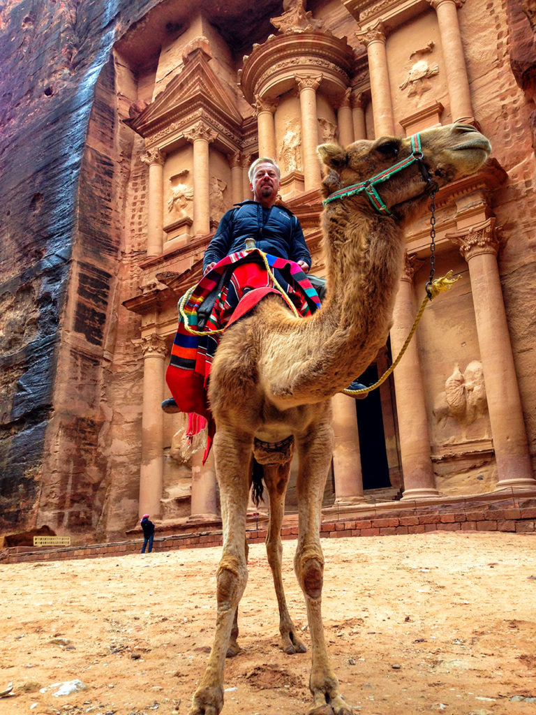 Astride a camel in front of the Treasury edifice in Petra Jordan