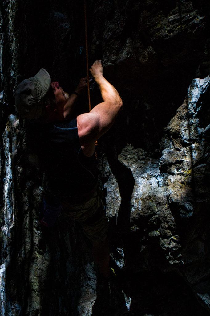 dramatic lighting frames rock climber