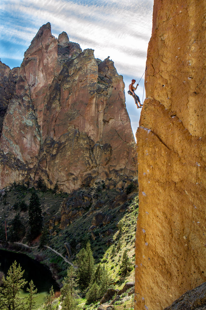 Climber takes a break high on the cliff at Smith Rock in Oregon