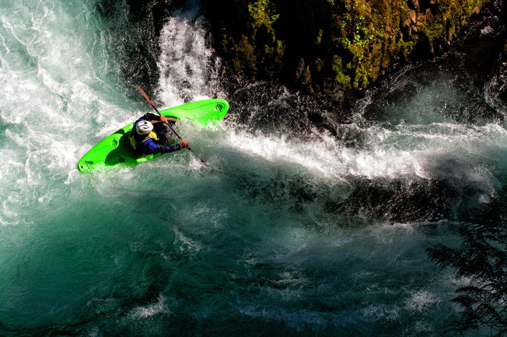 Downshot of whitewater kayaker navigating canyon rapids
