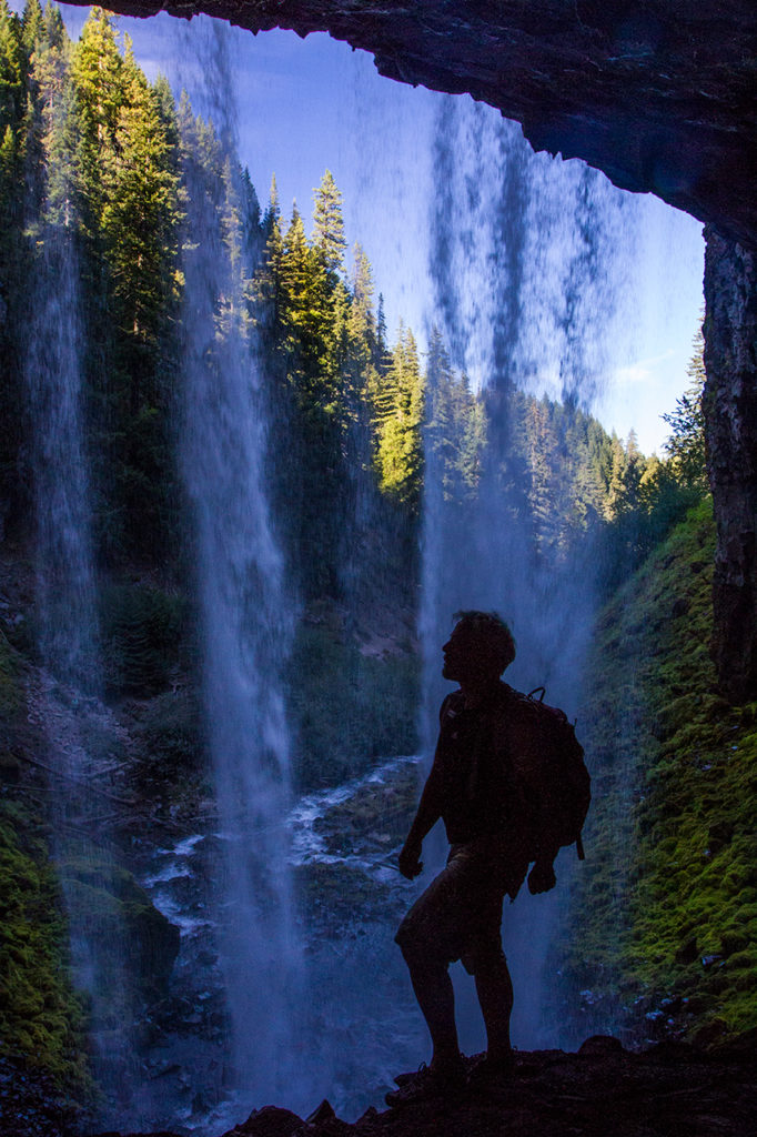 Silhouette of hiker behind the curtain of wilderness waterfall