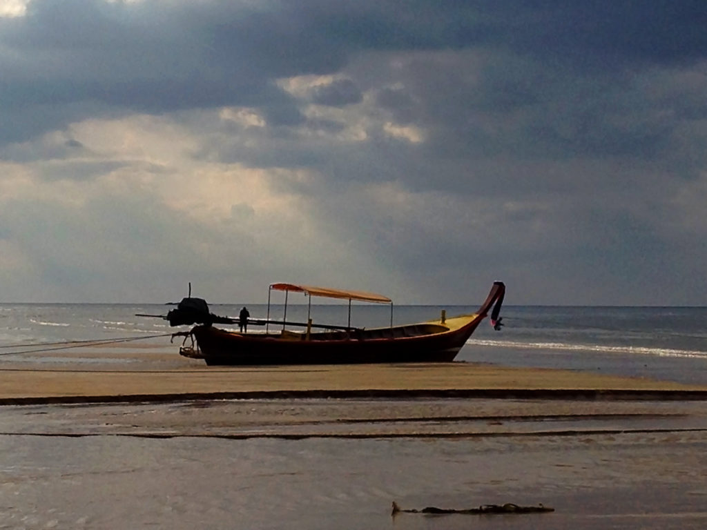 Longtail boat sits on the sand of a beautiful beach in Thailand
